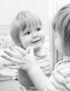 A girl looks in the mirror. Black and White image of baby.