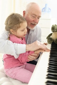 grandpa showing granddaughter how to play the piano