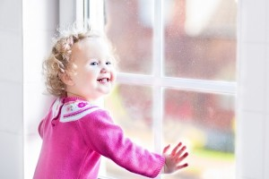 Beautiful little girl watching out of a window with autumn trees