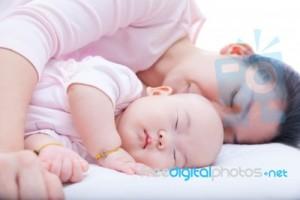 newborn-baby-girl-sleeping-in-mother-arm-100363509
