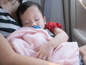 Baby sleep in car with dummy in mouth. Asian toddler sleep in her mom hand.